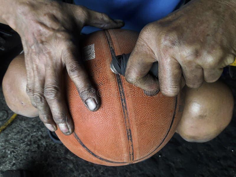Hand pumping up basketball stock photography