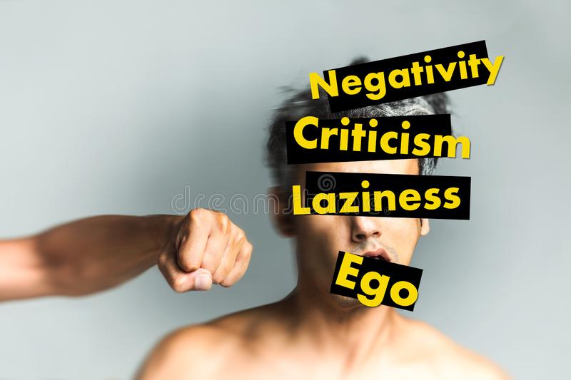 Hand punching face with yellow text on it. Hand punching a face with yellow text on it saying negativity, criticism, laziness, ego - Life improvement concept stock photo