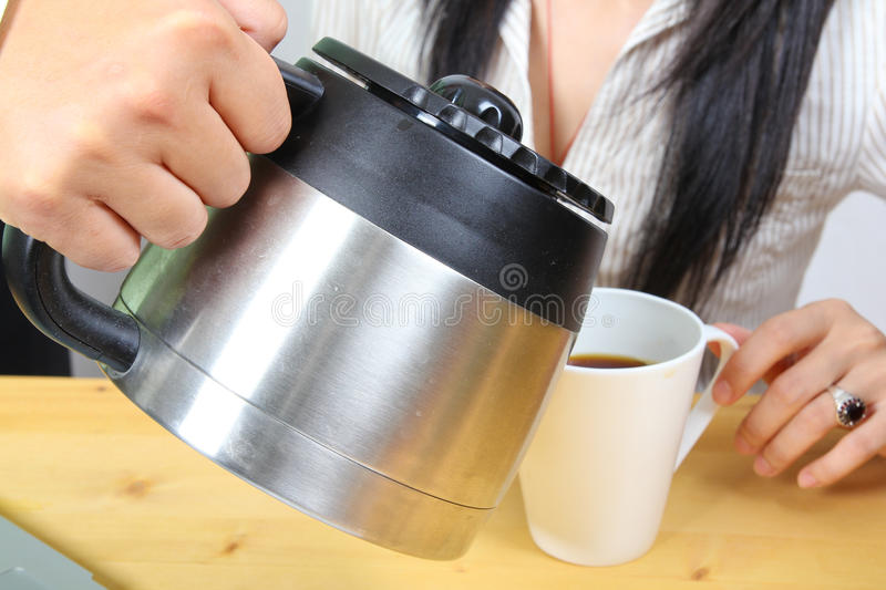 Hand puring coffee to a business woman stock photography