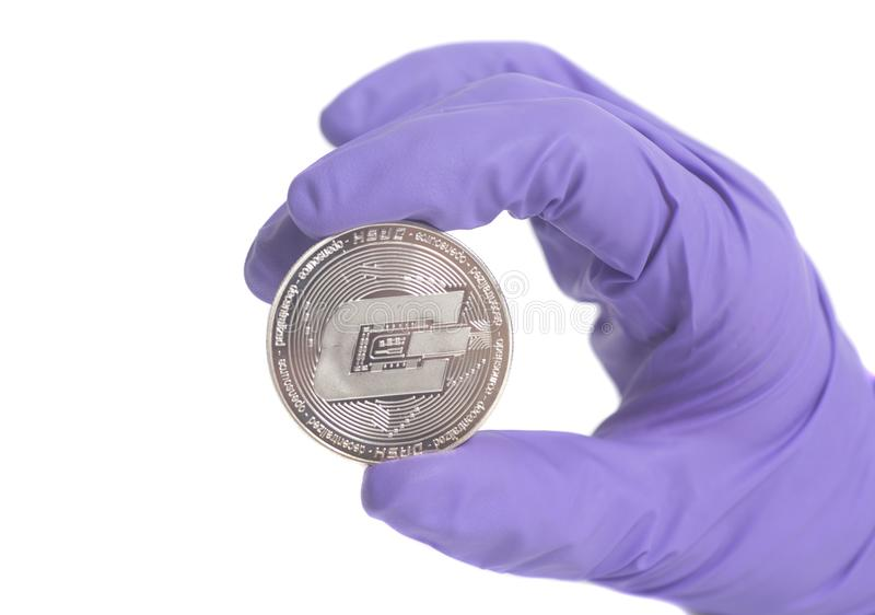 Hand in Purple Glove holds coin Dash Crypto Currency.Mining concept. Hand in Purple Glove holds silver Dash Crypto Currency isolated on a white background royalty free stock images