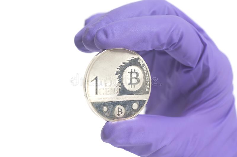Hand in Purple Glove holds silver bitcoin Crypto Currency.Mining concept. Hand in Purple Glove holds Silver Bitcoin Crypto Currency isolated on a white stock photography