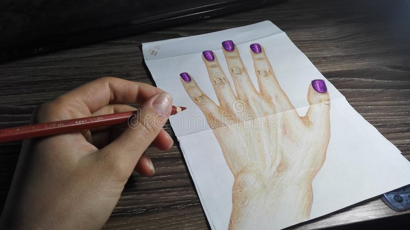 Hand with purple nails drawn by the real hand. Realistic drawing of hand with purple nails and the hand of the artist with the pencil stock images