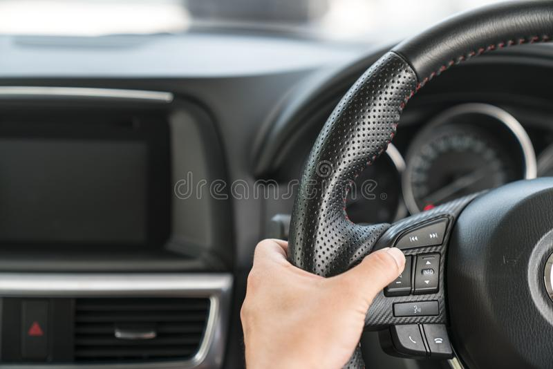 Hand pushes Cruise control buttons on modern car and speed limit stock image