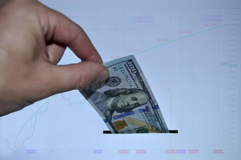The hand pushes $ 100 into the slot on the background of the financial chart stock photos
