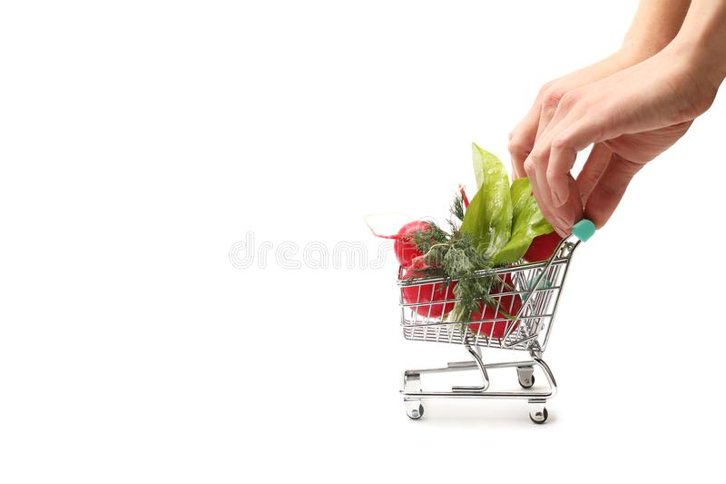 Hand pushing small shopping cart full with vegetables isolated on white background. Female hand pushing small shopping cart with radish and fresh leafs with royalty free stock photography