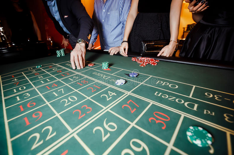 Hand put a bet on the roulette. Table, casino, people stock image