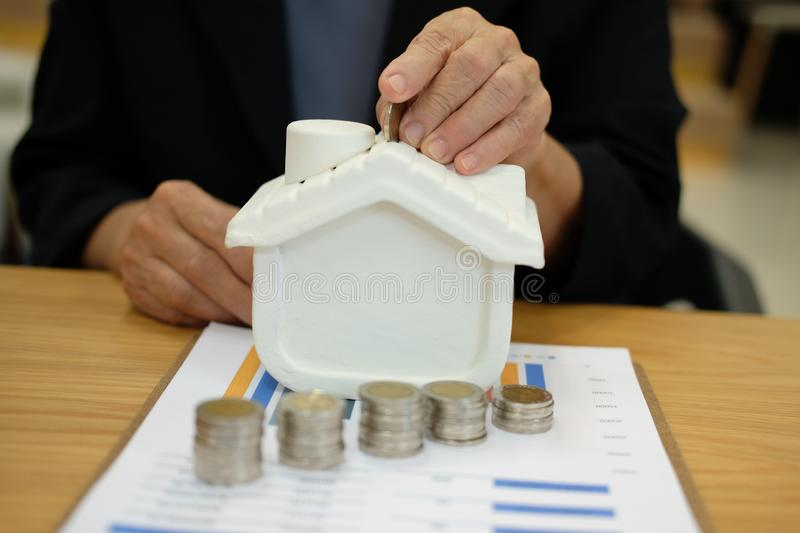 hand put coin on house model. coins stack & property purchase pl royalty free stock photo