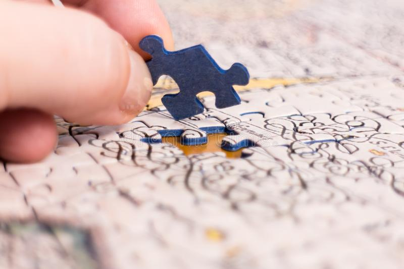 Hand put the last piece of jigsaw puzzle royalty free stock photography