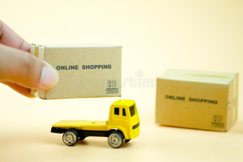 Hand put miniature cardboard boxes on yellow toy truck carries royalty free stock photos