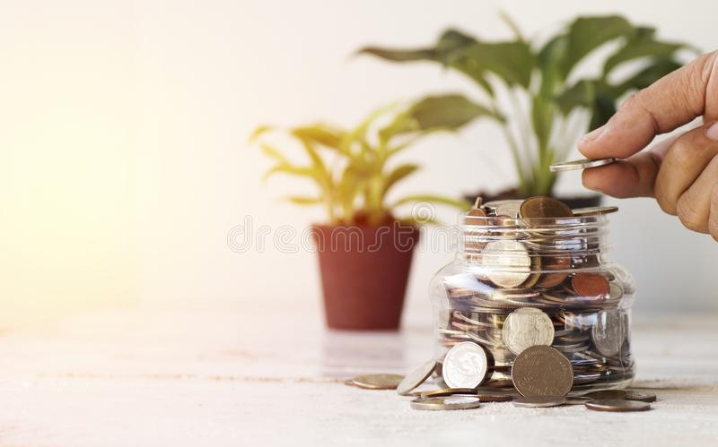Hand put money on bottle of coin, concept in save in business. Hand put money on bottle of coin, concept in save and growth in business royalty free stock photo