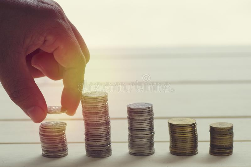 Hand put money coin deposit of save money for prepare in the future. save sign. With coin on table royalty free stock photography