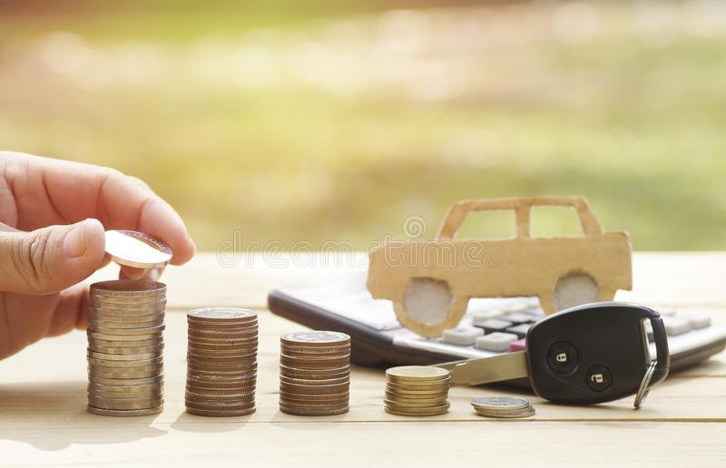 Hand put money on pile of coin with key of car. Concept in finance, save , buying and selling car stock photography