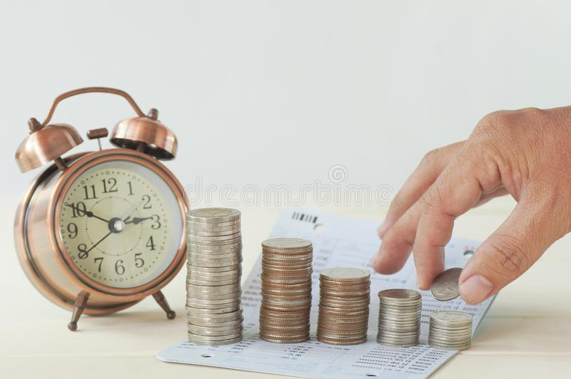 Hand put money on pile of coins with clock and book bank stock photo