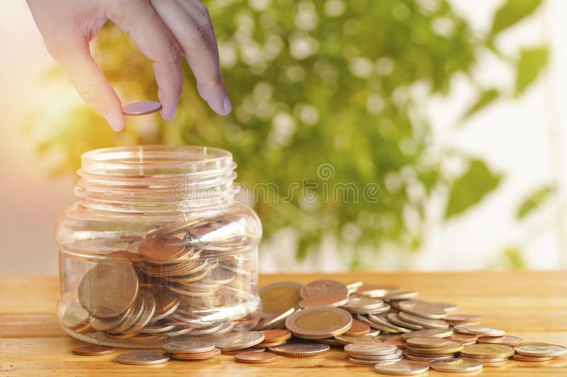 Hand put money on plastic jar and pile of coins, concept in growth, save and investment. In business stock image