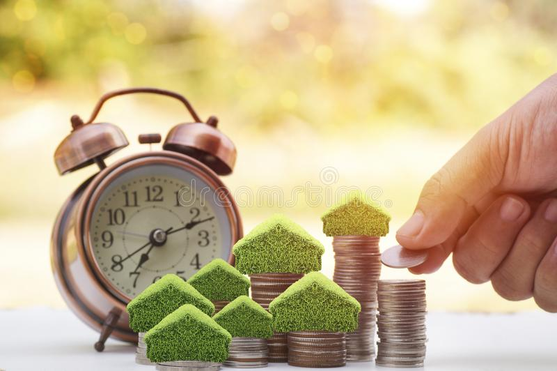 Hand put money on stacked of coins to save for house, small tree and home on pile with alarm clock on wood table with sunlight bac. Kground, concept as royalty free stock images