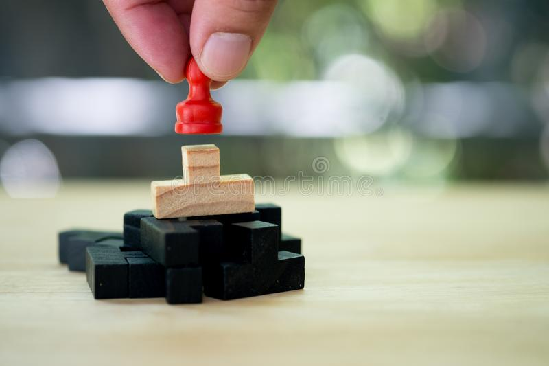 Hand put a red chess pawn on wooden puzzle. Against natural background for game plan and strategy concept royalty free stock images