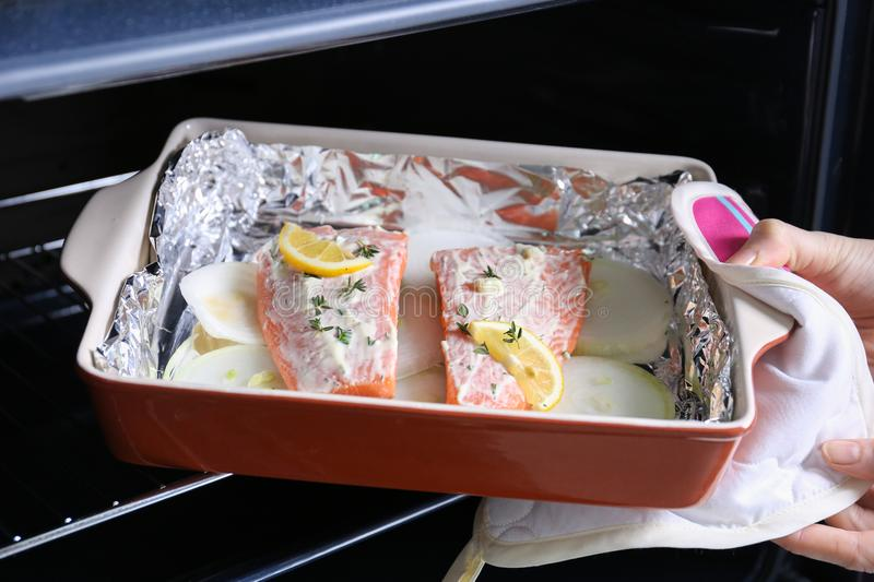 Hand putting baking dish with delicious salmon fillet stock images