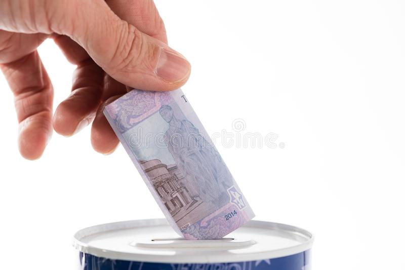 Hand putting bill into tin can saving bank royalty free stock photo