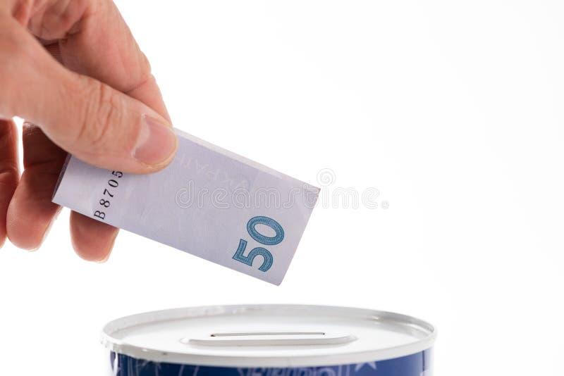 Hand putting bill into tin can saving bank stock image