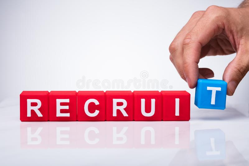 Hand Placing T Letter Of Word Recruit. Hand Putting Blue Block Near The Red Blocks To Complete Recruit Word stock photography