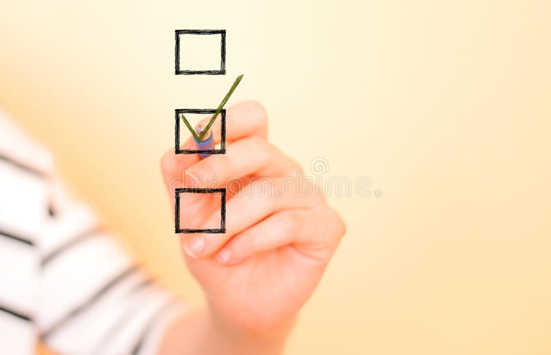 Hand putting check mark with pen stock photography