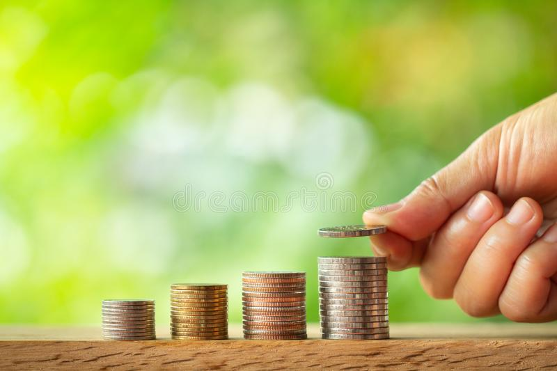 Hand putting coin on coins stack with greenery blurred background stock photo