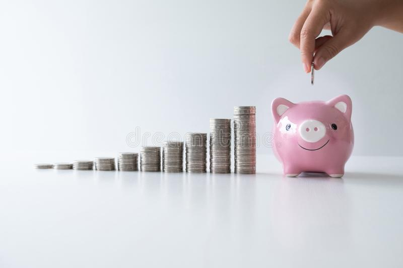hand putting coin into pink piggy bank with coins bar graph, step up start up business to success, Saving money for future royalty free stock image