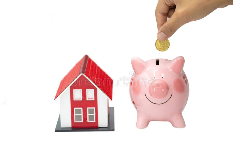 Hand putting a coin into a pink piggy bank thinking of buying a new house - saving money for future concept, isolated on white. Background stock photos
