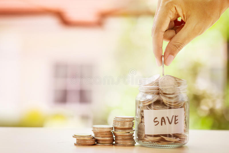 Hand putting Coins in glass jar and SAVE label with blur of house background for money saving for house or real estate loan royalty free stock photo