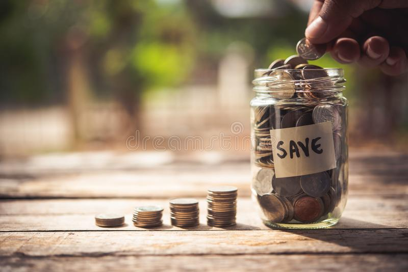 Hand putting coins in jar with money stack step growing growth royalty free stock photo