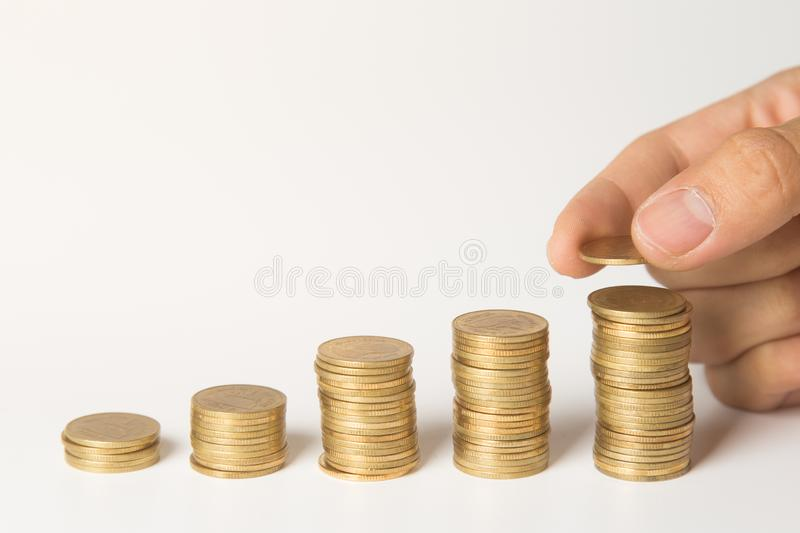 Hand putting coins on stack, Saving money and business concept stock images