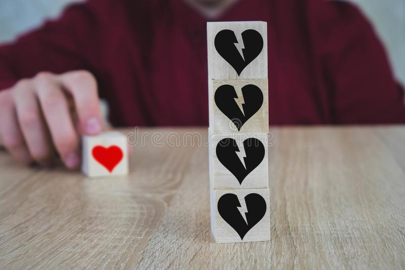 Hand putting the cube with a red heart symbol, which is opposite to black broken hearts on other wooden cubes royalty free stock images