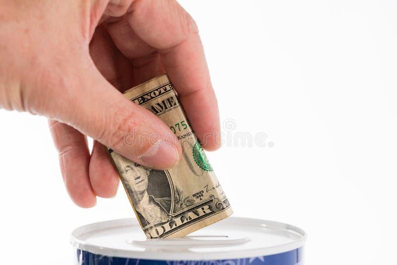 Hand putting dollar bill into tin can saving bank stock photography