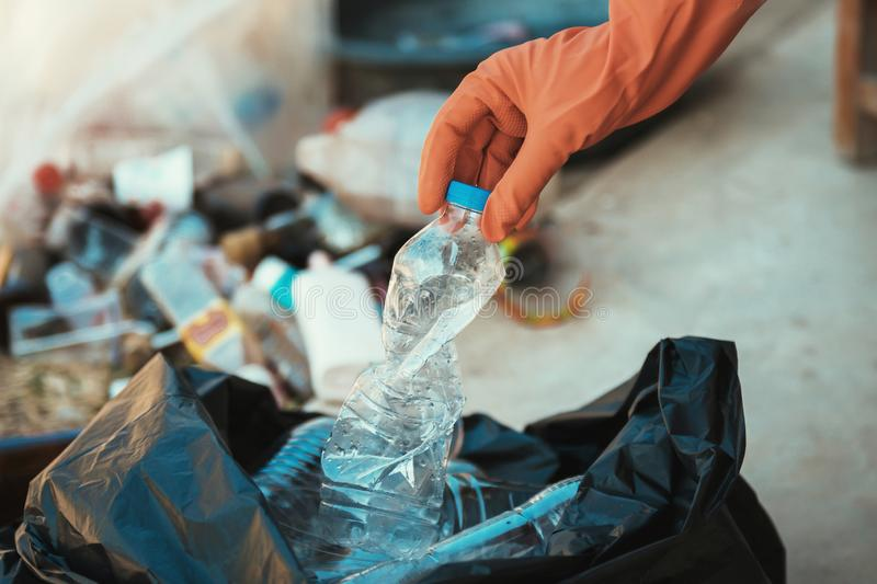 Hand putting empty plastic bottle in to garbage bag. Hand putting empty plastic bottle in to garbage black bag stock photo