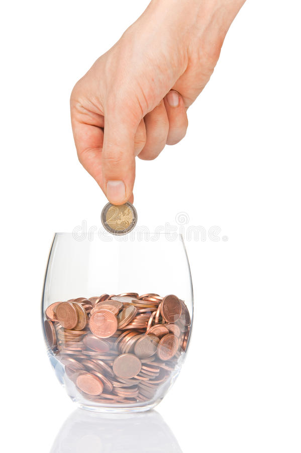 Hand putting 2 euro into glass with euro cents. Hand putting 2 euro coin into glass with euro cents isolated on white stock photo