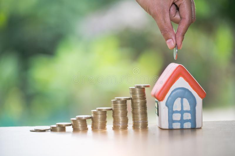Hand putting money coin stack with small house, purchase of habitation, buy a house,Risk, Assets, Property Investment, Saving stock image