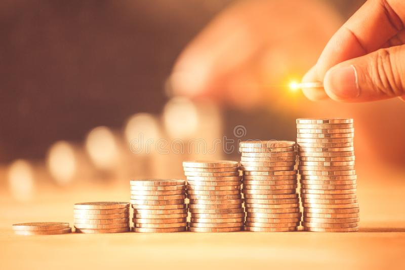Hand putting money coins stack for save money concept. Money management is growing a business. A hand putting money coins stack for save money concept. Money stock photography