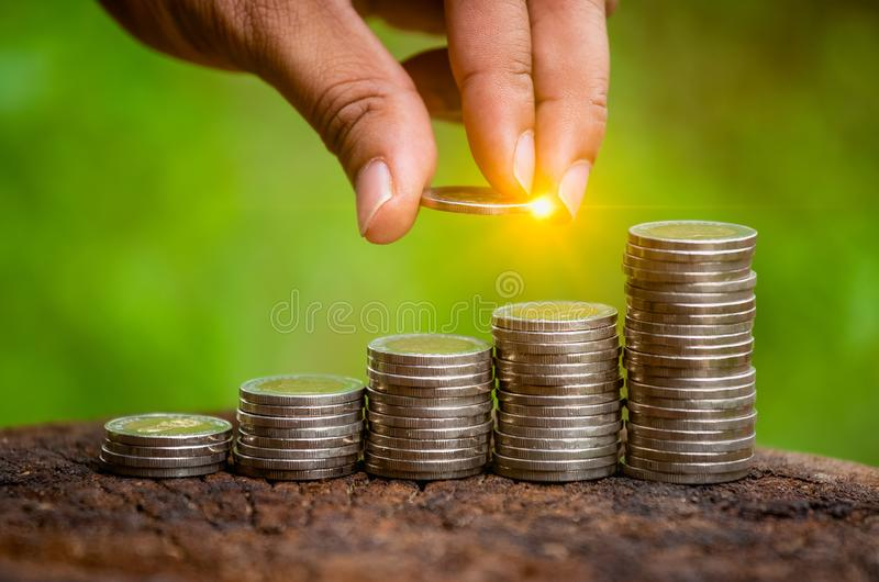 A hand putting money coins stack for save money concept. stock photo