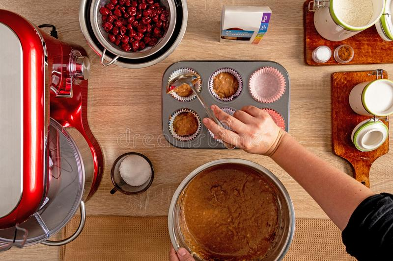 Hand putting muffin batter in baking tray stock images