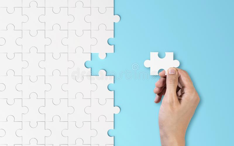 Hand putting a piece of white jigsaw puzzle. Pattern texture separated in strategy and solution of team business success stock photography