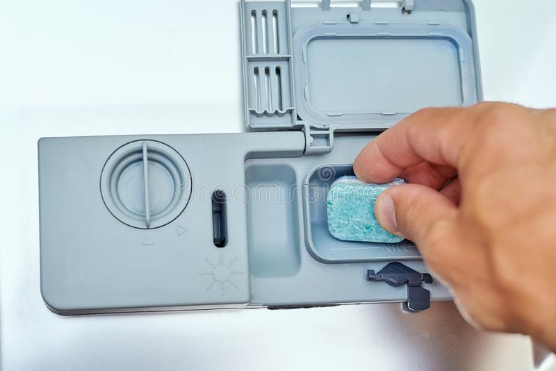 Hand putting soap tablet in the dishwasher machine, close up. Kitchen domestic appliance concept stock images