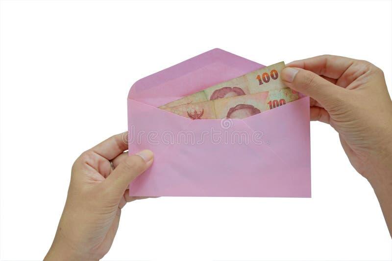 Hand putting Thai money in pink envelope stock photo
