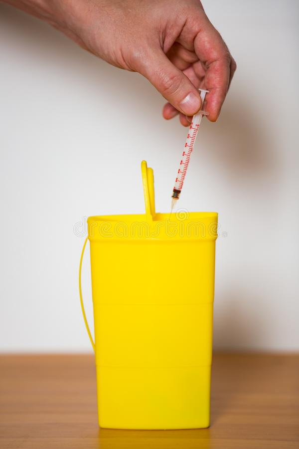 Hand putting used syringe with needle into yellow bin for safe disposal. royalty free stock photo