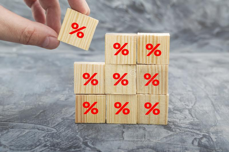 Hand putting wood cube block increasing on top with icon percentage symbol upward direction. Interest rate financial and mortgage rates concept royalty free stock photography