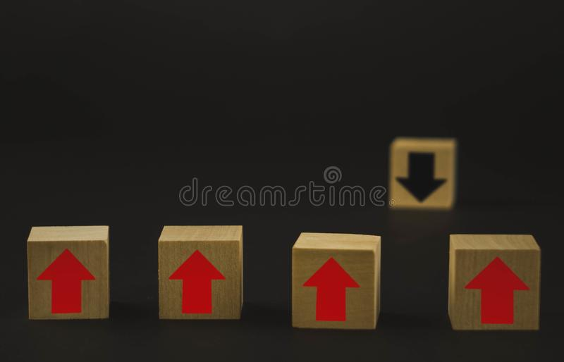 Hand putting wood cube block on top pyramid wooden blocks with red arrows facing opposite to the black arrows. With different stock photo