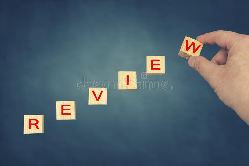 Hand putting wooden cube with alphabet REVIEW. Business concept stock images