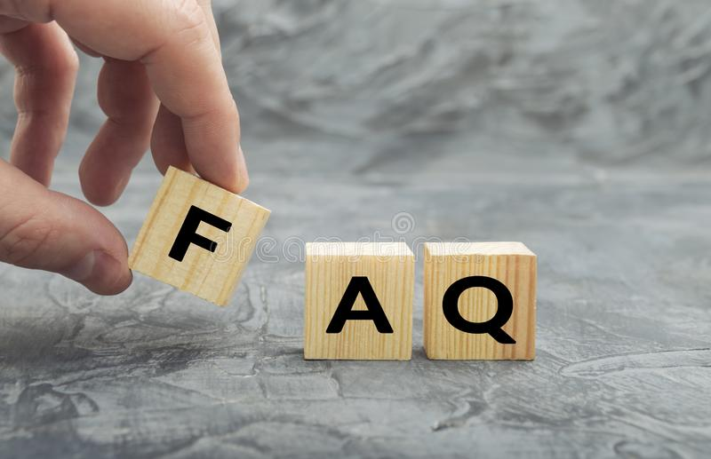 Hand putting wooden cube block with word FAQ  frequently asked questions stock image