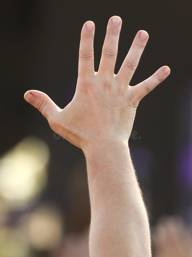 Hand raised up at a man at a concert stock photos