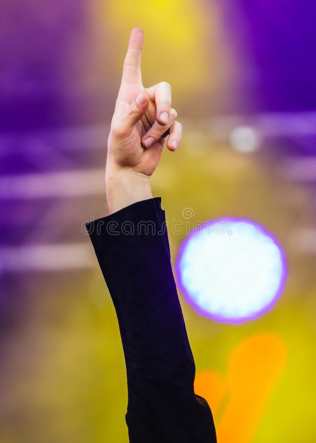 Hand raised up at a man at a concert stock photography
