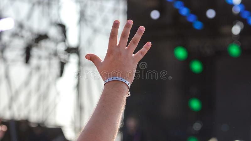 Hand raised up at a man at a concert stock photo